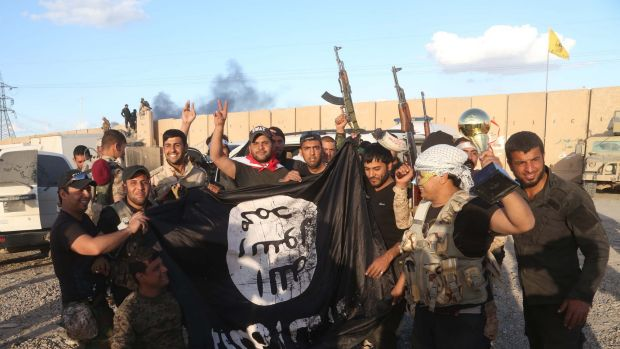Iraqi security forces and allied Shiite militiamen celebrate as they hold a flag of the Islamic State group they ...