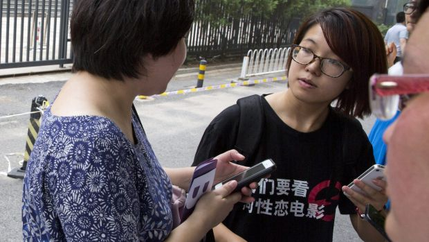 Women's rights activist Wei Tingting, right waits outside a court where the first court case in China involving ...