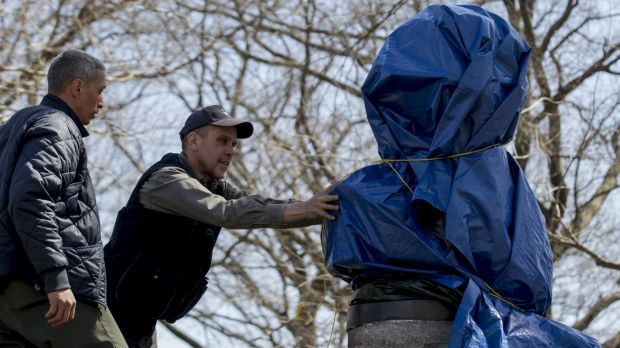 New York City Parks workers work to remove a covered large molded bust of Edward Snowden at Fort Greene Park in Brooklyn.