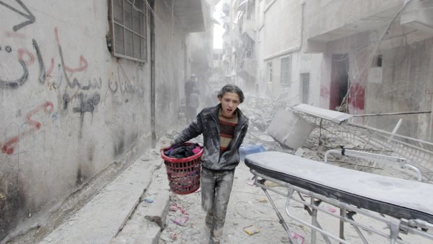 A boy carries his belongings at a site that was reportedly hit by a barrel bomb dropped by the Syrian Air Force in ...