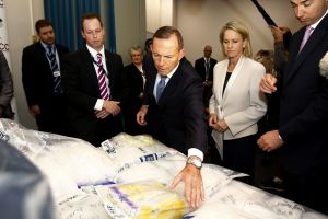 Prime Minister Tony Abbott inspects a haul of the drug ice during a press conference in Sydney on Wednesday.