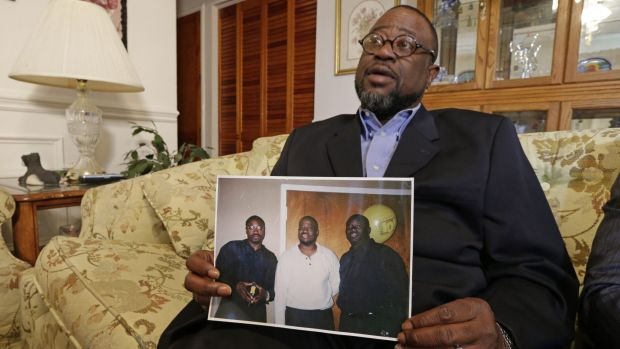 Anthony Scott holds a photo of himself, centre, and his brothers Walter (left) and Rodney, at his home near North ...