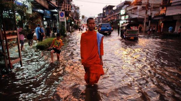 A Buddhist monk in a flooded street in central Bangkok. The government is struggling as Thailand experiences its worst ...