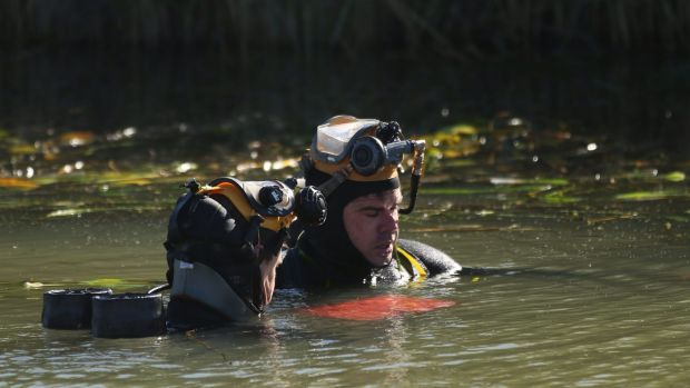 NSW police divers hold what appears to be a laptop submerged in an irrigation canal near Leeton, during their search for ...