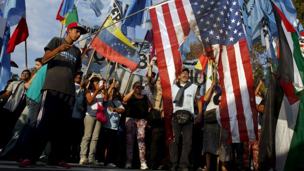 Supporters of Venezuela's President Nicolas Maduro shout slogans as they burn a US national flag during a demonstration ...