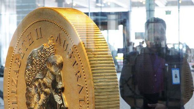 A security guard watches over the $1 million coin -- the biggest and heaviest in the world -- at the Commonwealth Heads ...