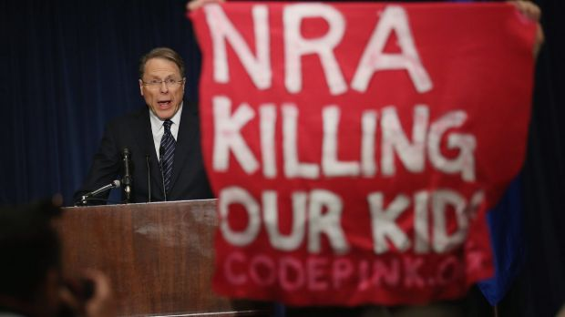 A demonstrator from an anti-gun lobby holds up a banner as NRA executive vice-president Wayne LaPierre speaks at a  news ...
