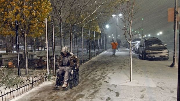 A man in a wheelchair makes his way to the homeless shelter in Salt Lake City as a major storm blows into Utah.