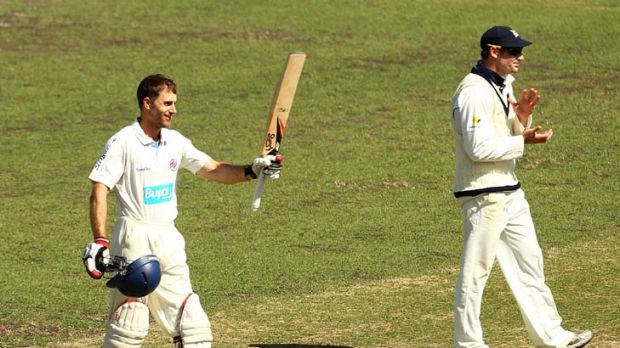 Run machine ... Simon Katich raises his bat after scoring a century against Victoria at the SCG yesterday.