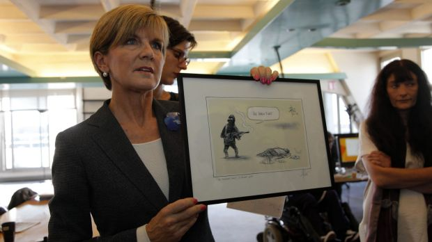 Julie Bishop shows off the cartoon before presenting it to the survivors of the <i>Charlie Hebdo</i> attack.