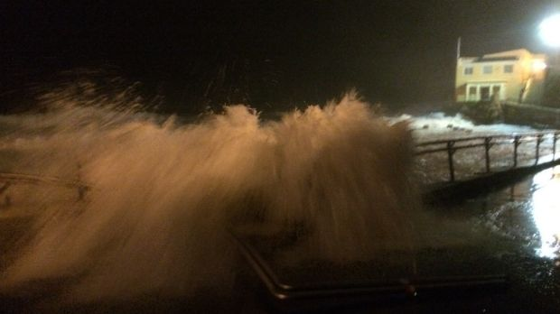 A huge wave smashes into and over the promenade at the south end of Coogee Beach, causing damage to the railing and ...