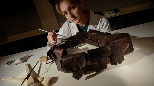Sophie Lewincamp (conservator) working on ammunition belt from Australian Lighthorse leather bandalier.