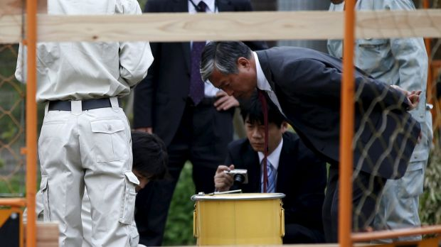 Workers of Tokyo's Toshima ward office and police officers check a container holding a fragment of an unknown object ...