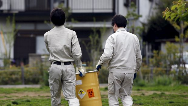 Workers of Tokyo's Toshima ward office carry away a container after it was dug up from the ground near playground ...