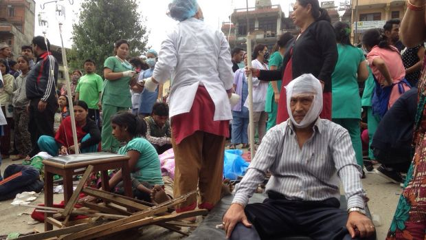 Injured people receive treatment outside the Medicare Hospital in Kathmandu, Nepal.