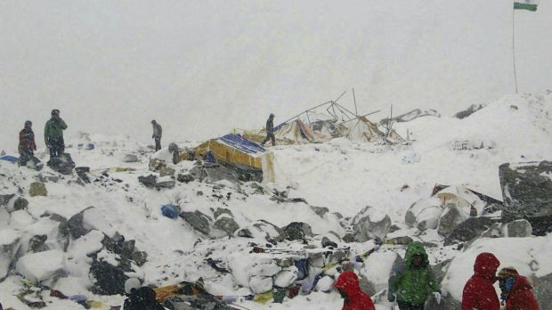 People approach the scene after an avalanche triggered by a massive earthquake swept across Everest Base Camp.