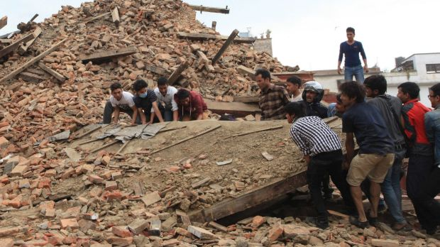People try to lift the debris from a temple at Hanumandhoka Durbar Square after an earthquake in Kathmandu.