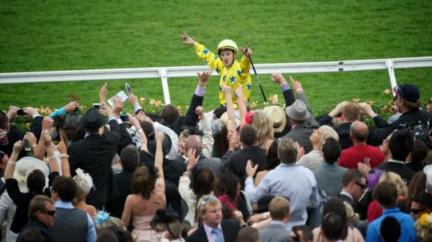 The crowd cheers Cristophe Lemaire after he rode Dunaden to a win at the Melbourne Cup.