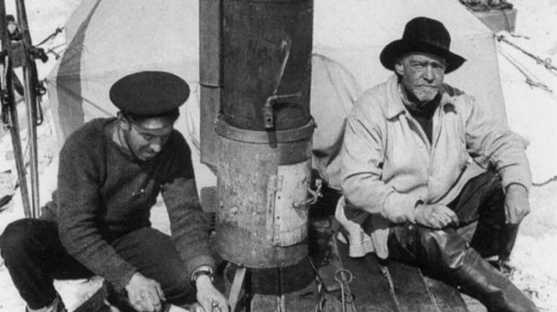 Photographer Frank Hurley, left, and Sir Ernest Shackleton sit before the entrance to their tent.