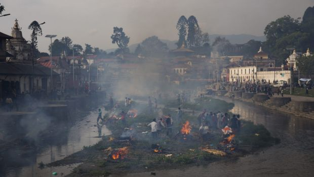 Flames rise from burning funeral pyres during the cremation of victims of the earthquake.