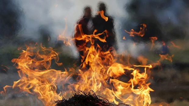 Family members stand next to the burning pyre of a family member at a cremation ground in Bhaktapur, Nepal. The death ...