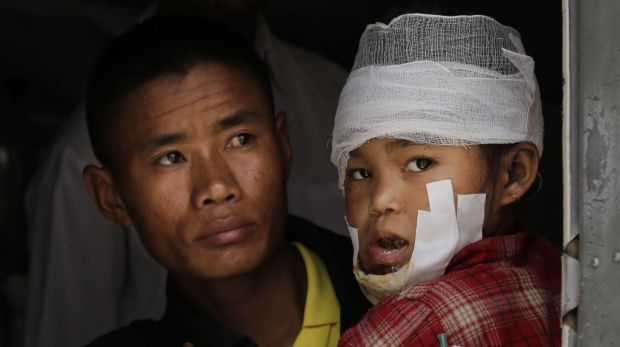 A child injured in Saturday's earthquake, is carried by a Nepalese soldier after being evacuated as they wait to ...
