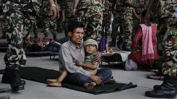 A man sits with a child on his lap as victims of Saturday's earthquake wait for ambulances after being evacuated to ...