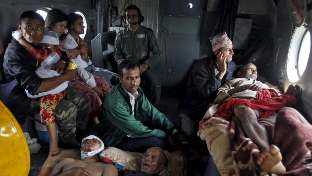 Victims of Saturday's earthquake rest inside an Indian Air Force helicopter as they are evacuated from Trishuli Bazar to ...