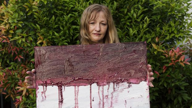 Sukumaran's painting teacher Tina Bailey holds a painting of the Indonesian flag dripping with blood, created on the day ...