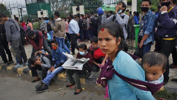 Nepalese people wait in Kathmandu on Wednesday to board buses to their villages.