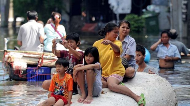 Afloat ... residents sit on a large piece of polystyrene foam during flooding in Bangkok