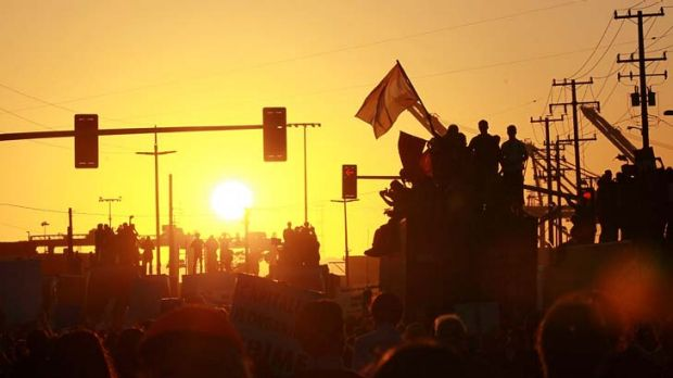 Demanding their share ... protesters mount tractor trailers loaded with shipping containers, raising their banners to ...
