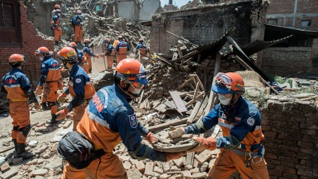 A Japanese disaster relief team remove debris from a collapsed building in Nepal.