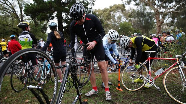 A cyclist fixes a puncture after hitting a tack during a protest that involved over 1000 bike riders who rode 13km's ...