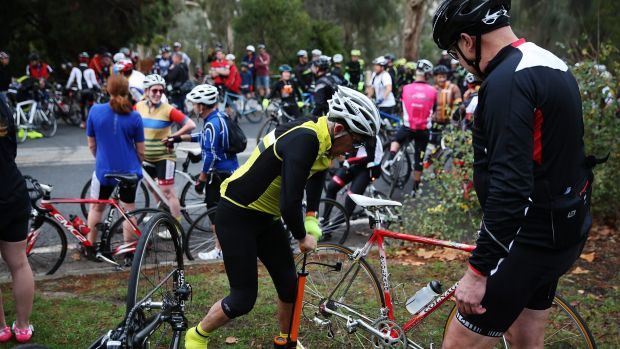 A cyclist fixes a puncture after hitting a tack on Kew Boulevard - during a protest involving over 1000 riders ...