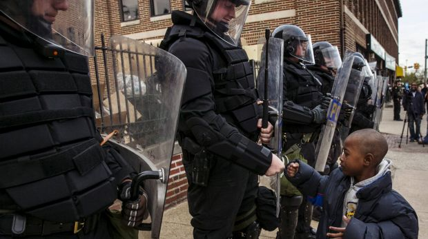 A young boy greets police officers in riot gear during a march in Baltimore after the decision to charge six officers, ...