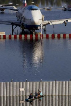 Marooned ... a plane sits stranded on the flooded tarmac at Bangkok's Don Muang airport.