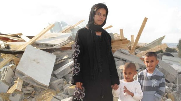 Demolished ... Rifa al-Oqbi and her sons Omar, 4, and Ali, 5, stand amid the ruins of their home, demolished by Israeli ...