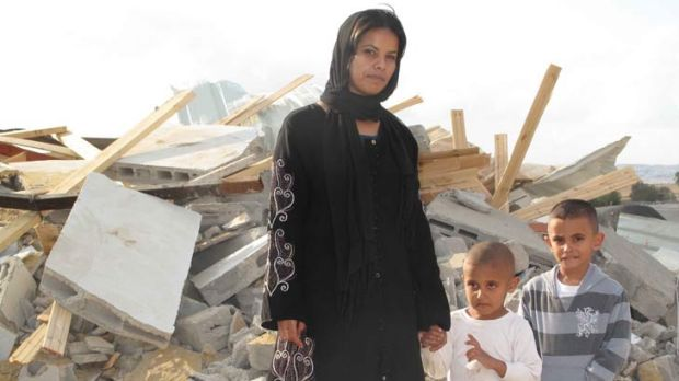 Rifa al-Oqbi and her two sons stand amid the rubble that was their home in the village of al-Qrain, in Israel's southern ...