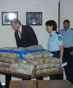 Cash haul ... police examine one of the syndicate's hoards of money found in numerous raids.