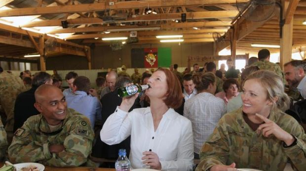 Prime Minister Julia Gillard drinks a Beck's Non-Alcoholic beer offered to her by Sergeant Vernon Pather (left) as ...