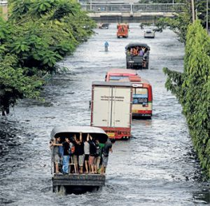 Amphibious transport: residents in Bangkok travel down an inundated street. Flooding has led to cancellation of the Loy ...