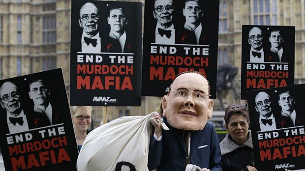 Hacked off … protesters, one in a James Murdoch mask, outside the Houses of Parliament in London.