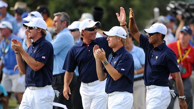 Team effort: Despite his ordinary day, Tiger Woods (right) was still able to join in the US celebrations with captain ...