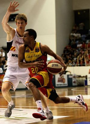 Patty Mills of the Tigers drives past Cameron Tovey of the Perth Wildcats.