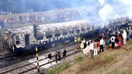 Firefighters work to extinguish a fire on the Howrah-Dehradun Express train between Gomo and Nimiaghat Railway stations ...