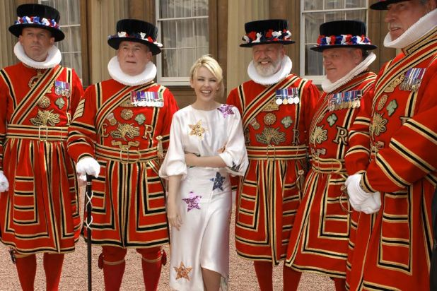 Kylie Minogue poses with Beefeatersafter receiving an OBE from Britain's Prince Charles for her services to music. July ...