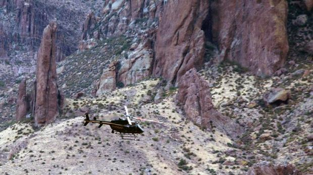 Six dead ... a Maricopa County Sheriff Police helicopter flies over the Superstition Mountains searching for victims.