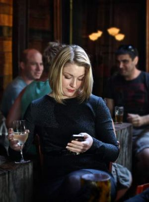 Stacey Brown uses her iPhone dating app at The Bridge Hotel, Richmond.