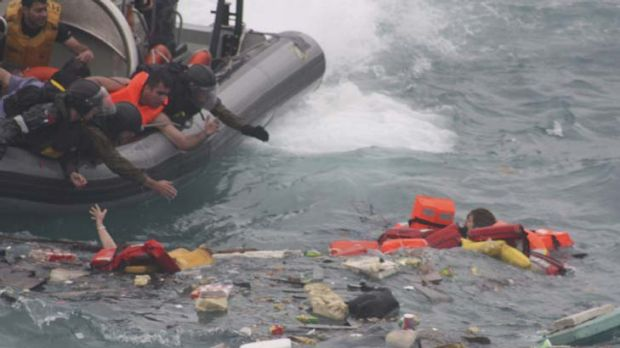 Rescuers reach out for the drowning asylum-seekers.